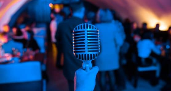 Microphone is on stage in a nightclub. Singer holds and sings into the microphone. Bright light of the club Shine on the MIC. Performances in the nightclub